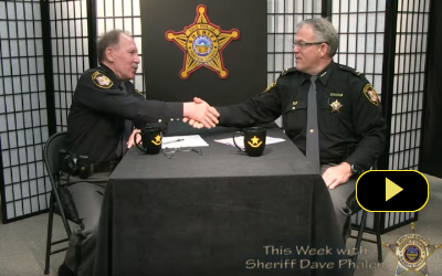 two sheriff officials shaking hands at table